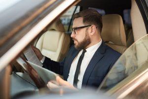 Mies istuu autossa ja lukee papereita